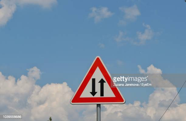 low angle view of road sign against cloudy sky - zuzana janekova stock pictures, royalty-free photos & images