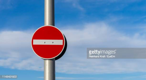 Low Angle View Of Road Sign Against Cloudy Sky