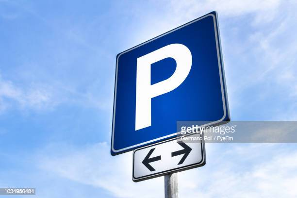 low angle view of road sign against sky - parking sign stock photos and pictures