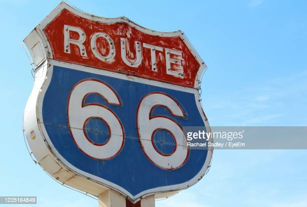low angle view of road sign against sky - route 66 stock-fotos und bilder