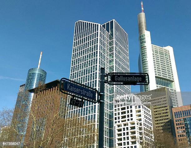 Low Angle View Of Road Sign Against Skyscrapers In City