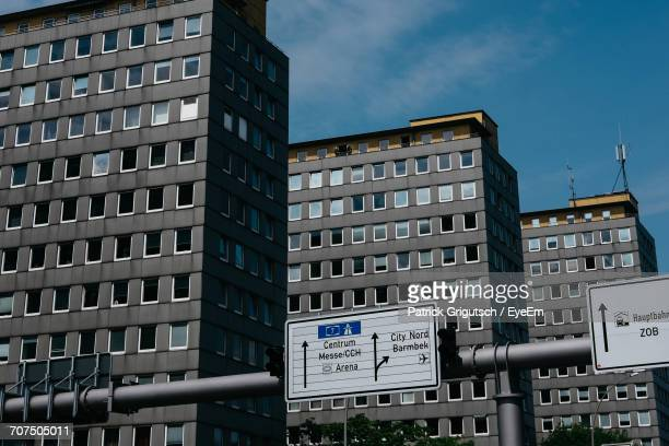 low angle view of road sign board on pole against residential buildings - close to stock pictures, royalty-free photos & images