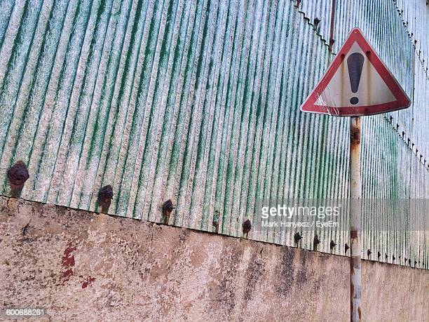 Low Angle View Of Road Sign By Wall