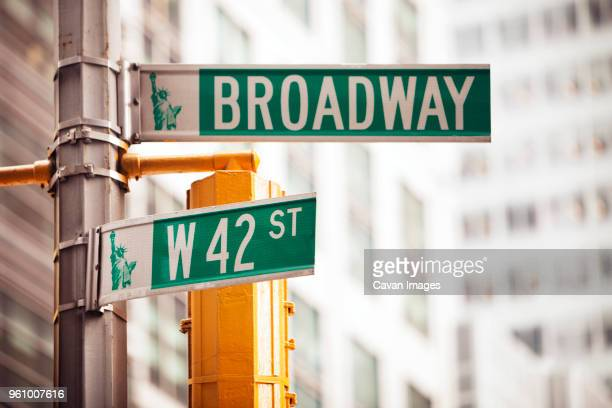 low angle view of road sign in city - road sign stock pictures, royalty-free photos & images