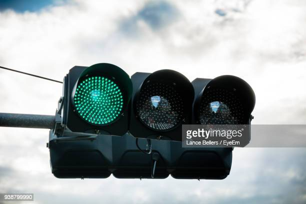 low angle view of road signal against cloudy sky - road signal stock pictures, royalty-free photos & images