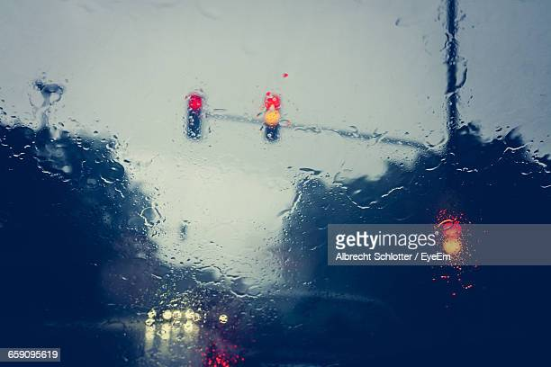 low angle view of road signals seen through glass windshield during rainy season - albrecht schlotter stock pictures, royalty-free photos & images