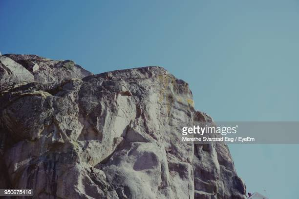 low angle view of rock formation against clear blue sky - scogliera foto e immagini stock