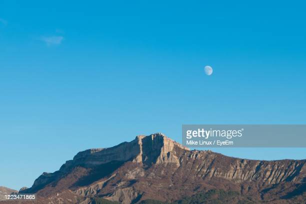 low angle view of rock formation against clear blue sky with moon - sisteron stock pictures, royalty-free photos & images