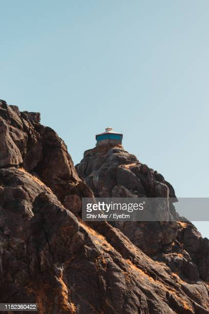 low angle view of rock formation against clear sky - junagadh stock photos and pictures