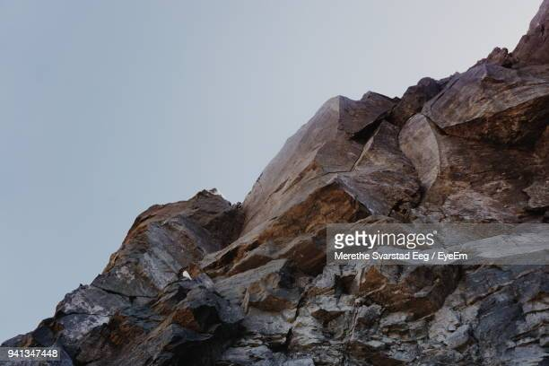 low angle view of rock formation against clear sky - rock wall stock pictures, royalty-free photos & images