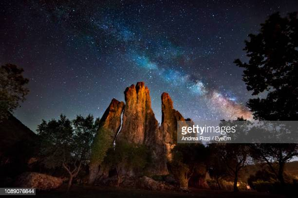 low angle view of rock formation against sky at night - andrea rizzi stockfoto's en -beelden