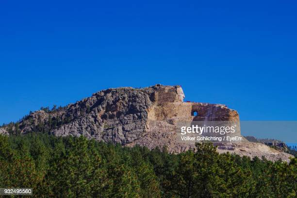 low angle view of rock formations against clear blue sky - black hills stock pictures, royalty-free photos & images