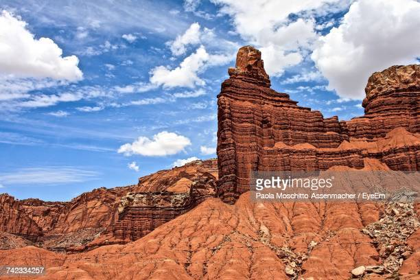 low angle view of rock formations against cloudy sky - capitol reef national park stock pictures, royalty-free photos & images