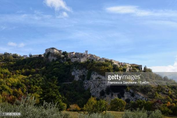 low angle view of rocks and trees against sky - molise foto e immagini stock