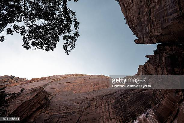 low angle view of rocky cliff against sky at zion national park - christian soldatke stock pictures, royalty-free photos & images