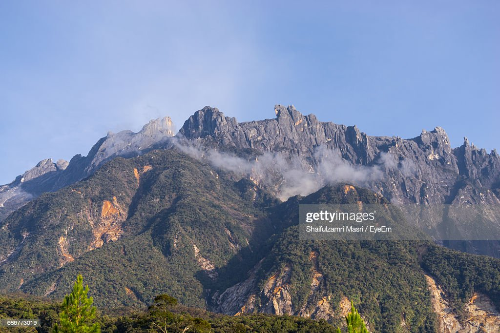 Low Angle View Of Rocky Mountain Against Clear Blue Sky : Stock Photo