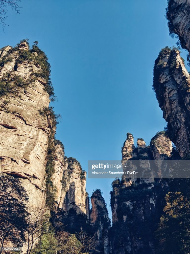 Low Angle View Of Rocky Mountains Against Clear Blue Sky : Stock Photo