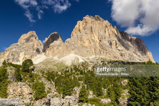 low angle view of rocky mountains against sky,canazei,trentino,italy - カナツェイ ストックフォトと画像