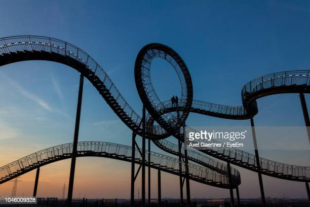 low angle view of rollercoaster against blue sky - duisburg imagens e fotografias de stock