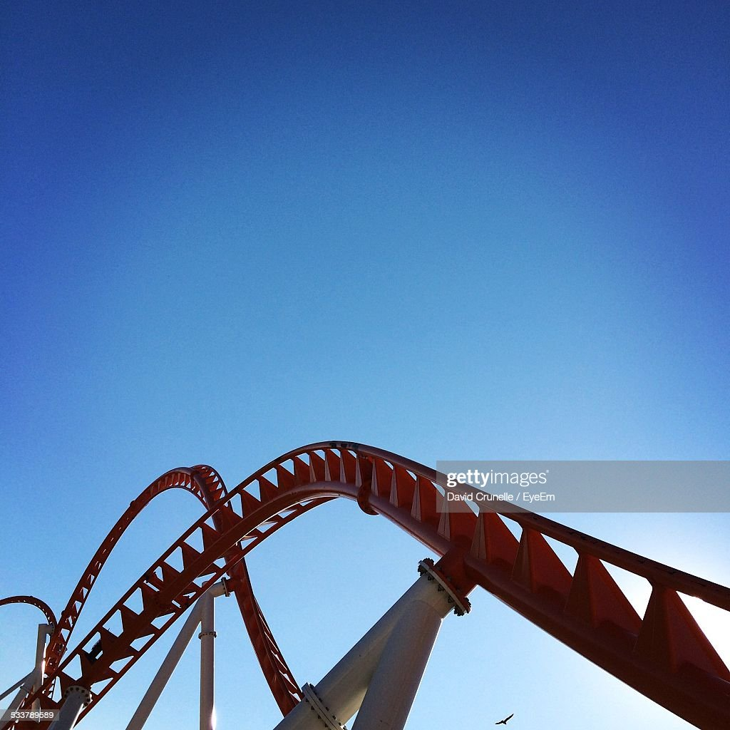 Low Angle View Of Rollercoaster Against Clear Blue Sky : Foto stock