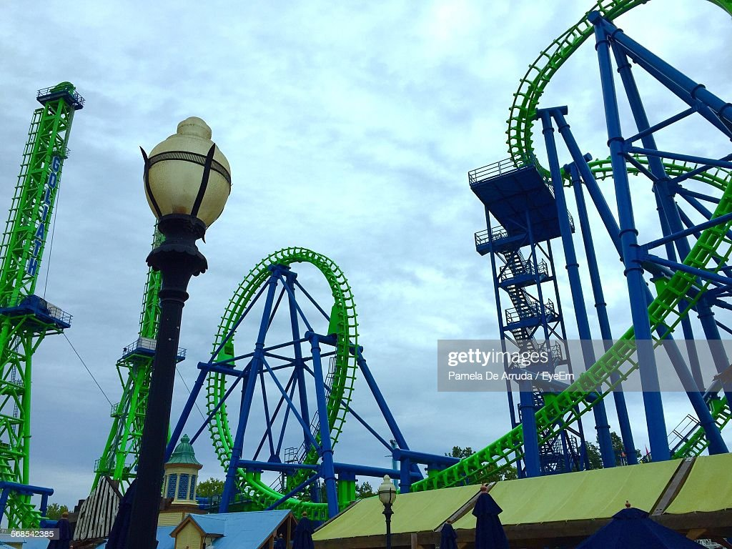 Low Angle View Of Rollercoaster Ride In Amusement Park Against Cloudy Sky : Foto de stock
