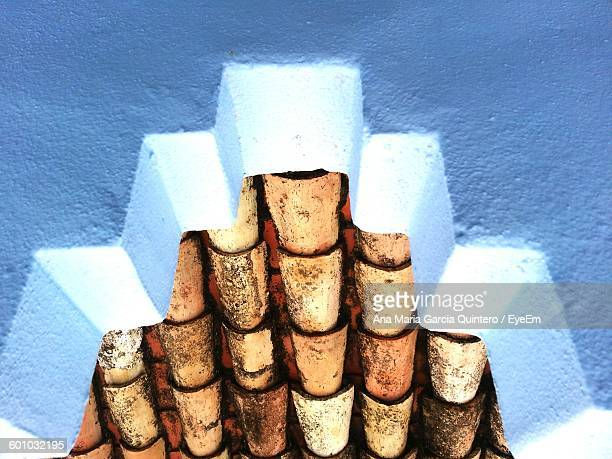 Low Angle View Of Roof Tiles Seen From Hole In White Wall