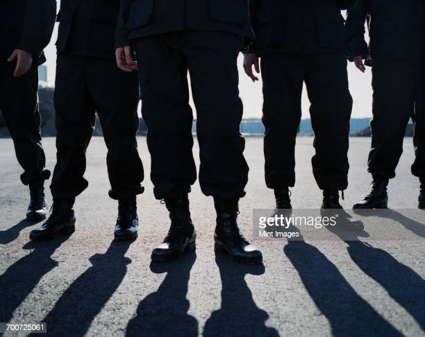 low angle view of row of men wearing military uniforms, casting shadows - paramilitary stock pictures, royalty-free photos & images