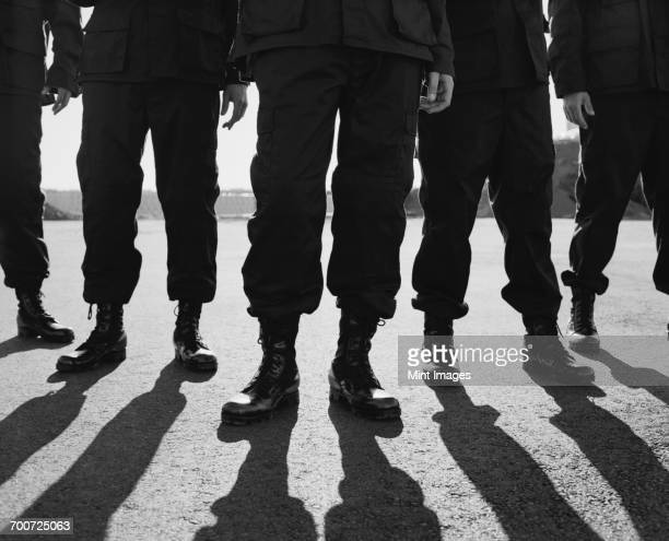 low angle view of row of men wearing military uniforms, casting shadows - militia stock pictures, royalty-free photos & images