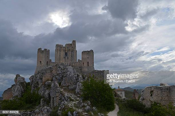Low Angle View Of Ruined Rocca Calascio Against Cloudy Sky