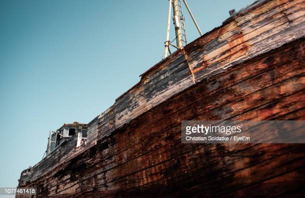 low angle view of rusty boat against clear sky - christian soldatke stock-fotos und bilder