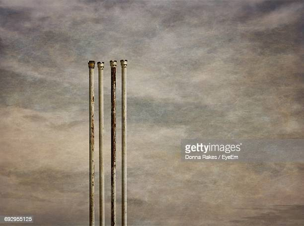Low Angle View Of Rusty Metallic Poles Against Cloudy Sky