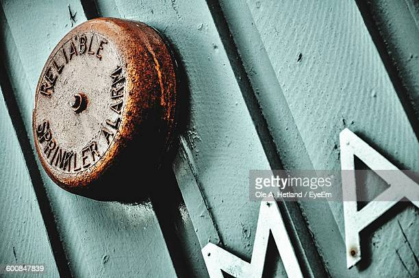 Low Angle View Of Rusty Metallic Sprinkler Alarm On Wooden Wall