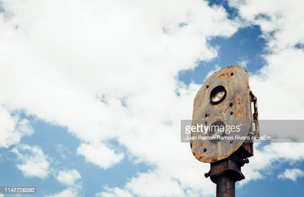 Low Angle View Of Rusty Road Signal Against Sky