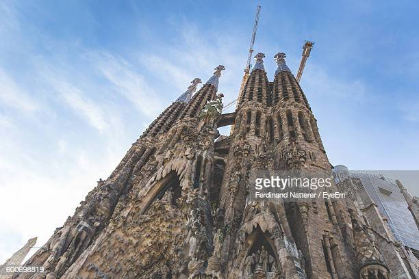 Low Angle View Of Sagrada Familia With Cranes Against Sky