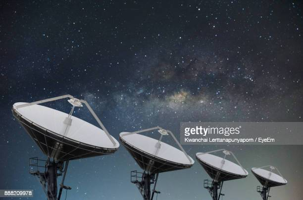 low angle view of satellite dishes against star field - receiver stock pictures, royalty-free photos & images