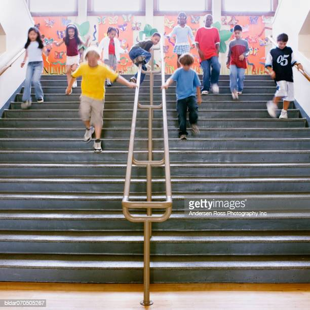 Low angle view of school children running down the stairs