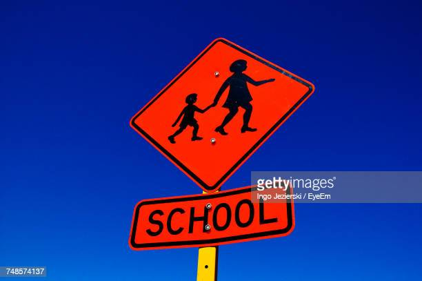 Low Angle View Of School Crossing Sign Against Clear Blue Sky