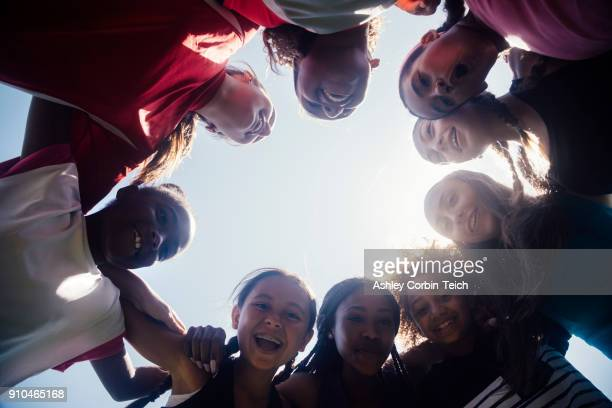 low angle view of schoolgirl soccer team huddled in circle - images stock pictures, royalty-free photos & images