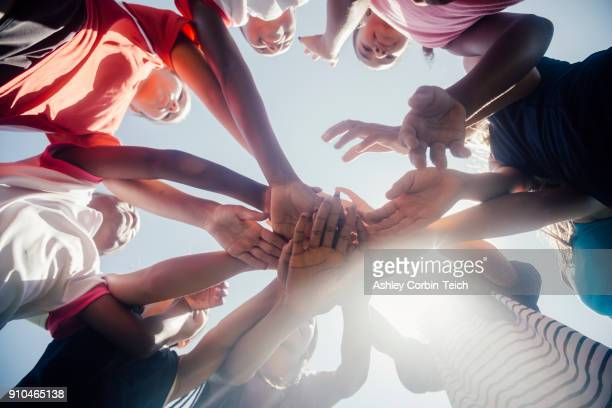 Low angle view of schoolgirl soccer team in circle with hands together