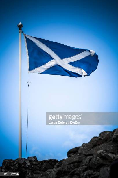 Low Angle View Of Scottish Flag Waving Against Blue Sky
