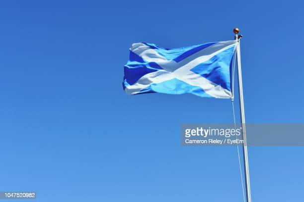 low angle view of scottish flag waving against clear blue sky during sunny day - scotland flag stock photos and pictures