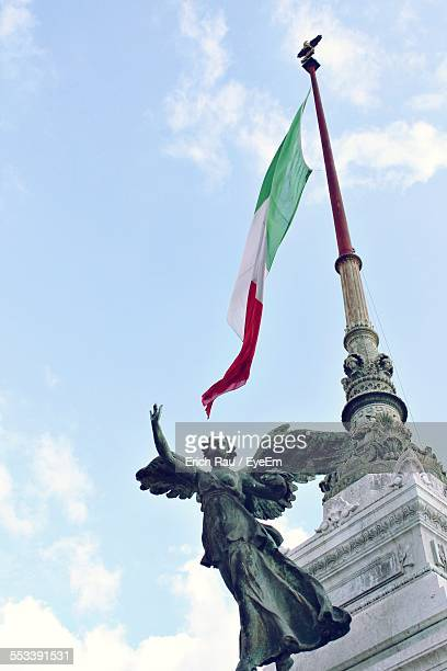 Low Angle View Of Sculpture And National Flag