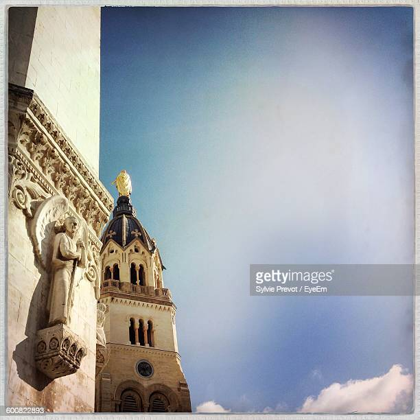 Low Angle View Of Sculpture On Basilica Of Notre Dame De Fourviere Against Sky