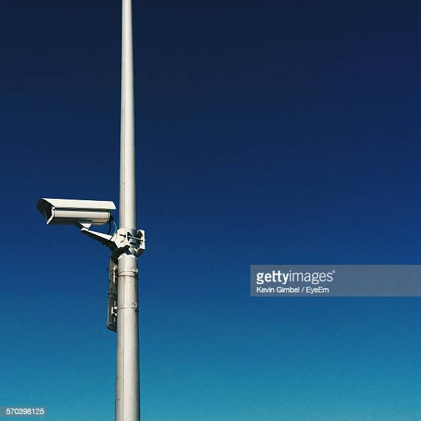 Low Angle View Of Security Camera Against Clear Blue Sky
