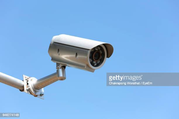 low angle view of security camera against clear blue sky - security camera stock pictures, royalty-free photos & images