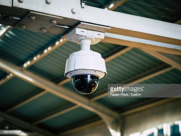 low angle view of security camera hanging from ceiling in train station, berlin - big brother orwellian concept stock pictures, royalty-free photos & images