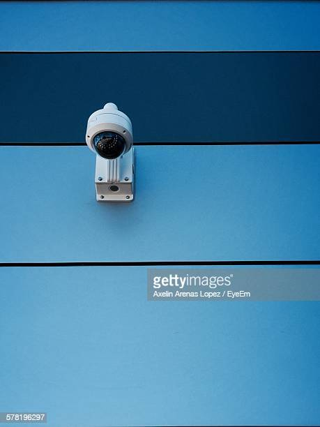 Low Angle View Of Security Camera On Blue Wall