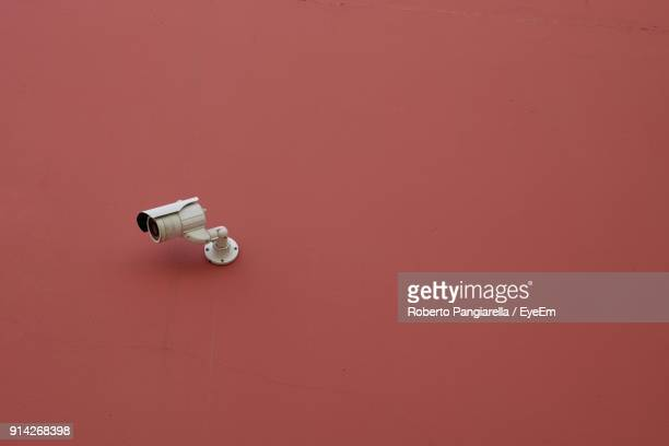 Low Angle View Of Security Camera On Brown Wall