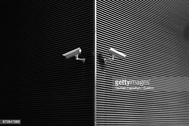 low angle view of security cameras on wall - spionage und aufklärung stock-fotos und bilder