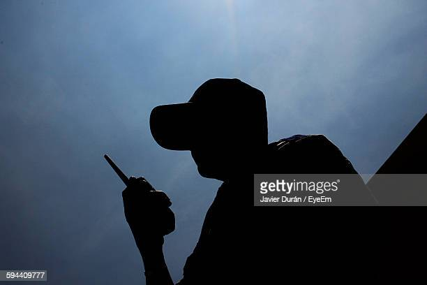 low angle view of security guard with walkie-talkie against sky - watchmen stock pictures, royalty-free photos & images